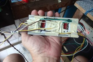 Back of PVC board. The low voltage wires were insulated from one other and gummed to the pvc casing by masking tape, so that power cables would be placed away from signal wires as much as possible.